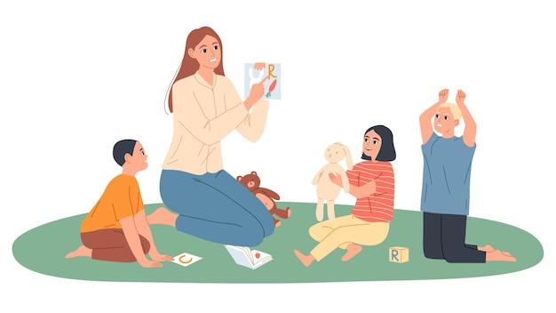 L'institutrice de maternelle joue avec les enfants, elle leur montre des images avec des lettres.
