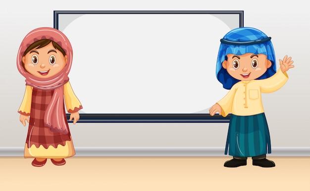 Irag enfants debout devant le tableau blanc