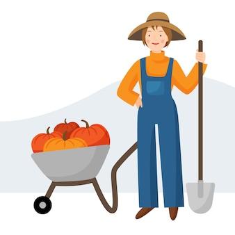 Jardinière fille dans un chapeau et une salopette une agricultrice se tient avec une pelle chariot de jardin avec citrouille