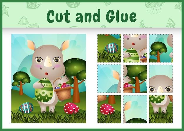 Jeu de société pour enfants couper et coller sur le thème de pâques avec un joli rhinocéros tenant l'œuf de seau et l'œuf de pâques