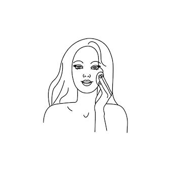 La jeune belle femme essuie son visage avec un démaquillant d'éponge