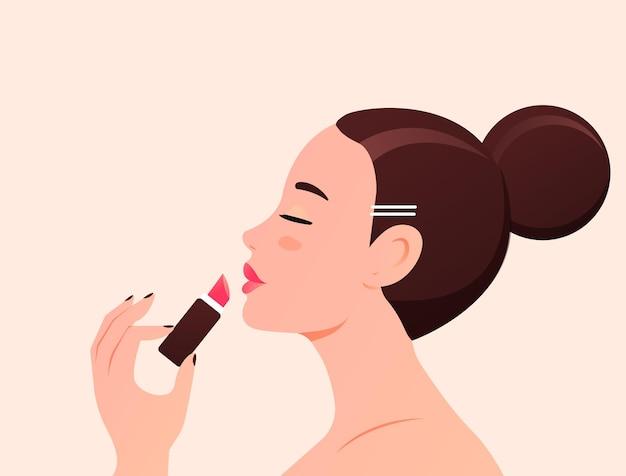 La jeune belle femme peint des lèvres avec un rouge à lèvres