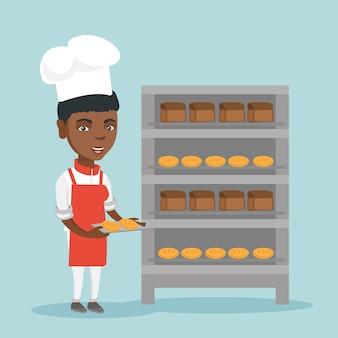 Jeune boulanger africain tenant un plateau avec du pain.