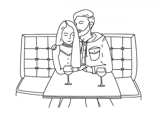 Jeune couple est assis dans un café et boit du vin.