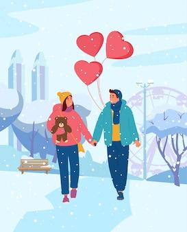 Jeune couple main dans la main avec des ballons en forme de coeur marchant dans le parc d'hiver