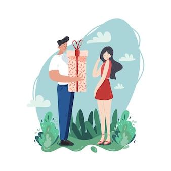 Un jeune couple passe son temps ensemble. l'homme donne un cadeau à sa petite amie embarrassée. un amour pur et une bonne relation.