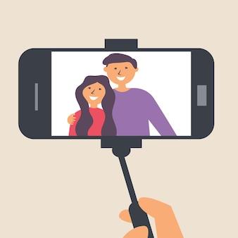 Le jeune couple prend des photos sur un bâton de selfie