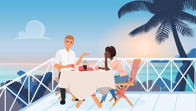 Jeune couple à un rendez-vous dans un restaurant près de l'océan pendant le coucher du soleil