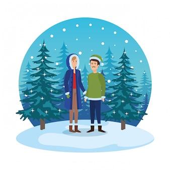 Jeune couple avec des vêtements d'hiver dans le paysage de neige