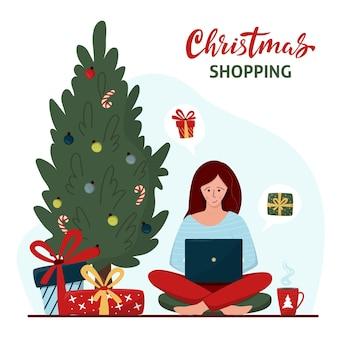 Une jeune femme achète des cadeaux de noël en ligne. arbre de noël décoré et femme avec ordinateur portable.