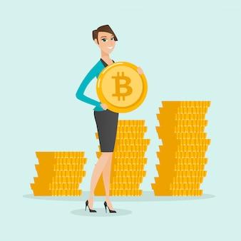 Jeune femme d'affaires réussie avec une pièce de monnaie bitcoin.