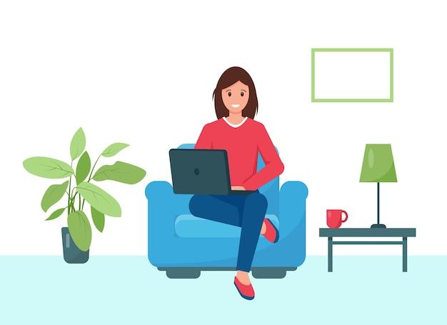 Jeune femme assise dans un fauteuil et travaillant ou apprenant en ligne à la maison.