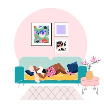 Jeune femme blonde portant sur un canapé à la maison. la belle au bois dormant. restez à la maison. protégez-vous et protégez les autres. intérieur de l'appartement moderne .cadres sur un mur et plante d'intérieur dans un vase.