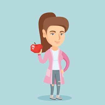 Jeune femme caucasienne tenant une pomme.
