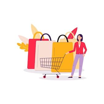 Une jeune femme en costume se tient près d'un chariot de supermarché ou d'un chariot et de sacs à provisions.