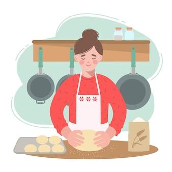 Jeune femme dans la cuisine prépare des petits pains moelleux. elle a la pâte dans ses mains.