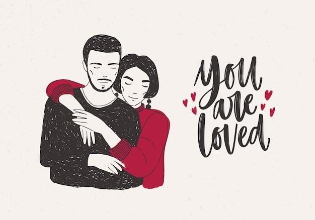 Jeune femme debout derrière l'homme et l'embrassant chaleureusement et vous êtes aimé lettrage à la main décoré de petits coeurs. aimer couple romantique