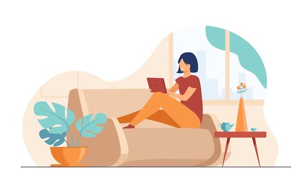 Jeune femme, délassant, à, sofa, à, ordinateur portable