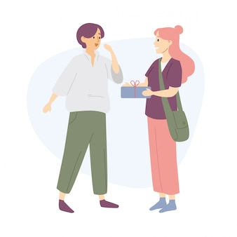Jeune femme donnant une boîte à un ami