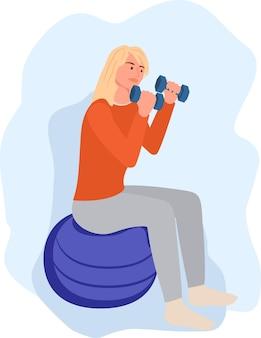 Une jeune femme est assise sur un ballon et lève des haltères dans ses mains la fille fait du sport