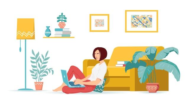 Une jeune femme est assise sur un canapé et travaille à domicile avec un ordinateur portable salon moderne et confortable