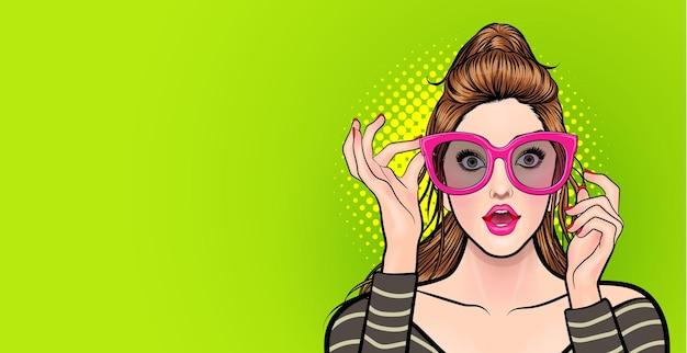Jeune femme étonnée dans des verres pointant quelque chose de style bande dessinée pop art.