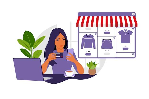 Une jeune femme fait des achats en ligne à l'aide d'un ordinateur portable. payez vos achats avec une carte de crédit sur internet. le concept des paiements en ligne et des achats électroniques, des achats. plat.