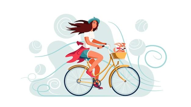 Jeune femme fait du vélo avec un chien dans un panier.