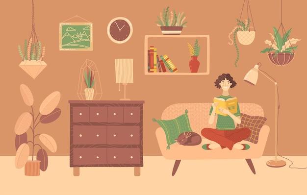Jeune femme lisant un livre à la maison sur un canapé