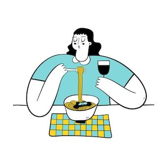 Jeune femme mangeant des pâtes et buvant du vin