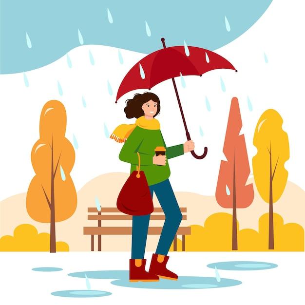 Jeune femme avec parapluie marchant sous la pluie en automne
