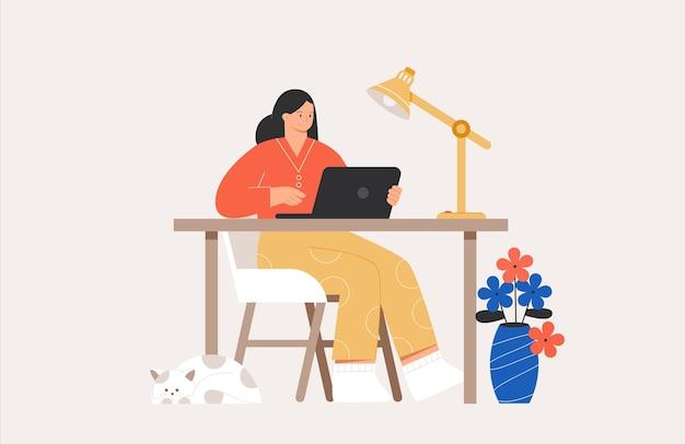Jeune femme ou pigiste travaillant ou étudiant en ligne avec un ordinateur portable à la maison.