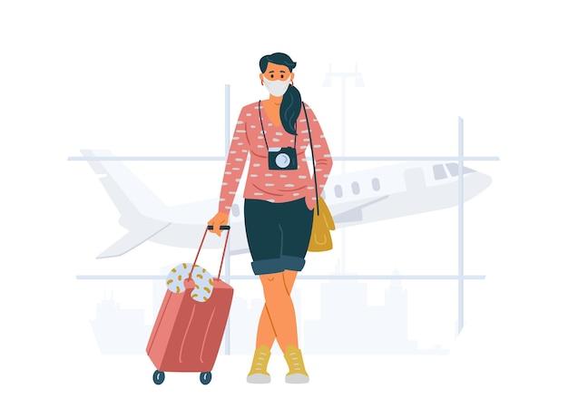 Jeune femme portant un masque de protection avec valise et appareil photo debout dans les voyages à l'aéroport pendant le concept de pandémie