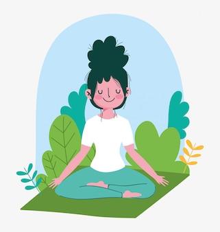 Jeune femme pratiquant le yoga en lotus posant sur un tapis en plein air