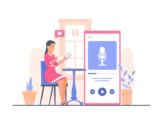 Une jeune femme en robe rose est assise à une table de café en train de boire du café et d'écouter un podcast à l'aide d'un smartphone