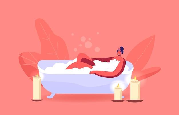 Jeune femme se détendre dans le bain avec de la mousse et des bougies allumées au spa ou à la maison