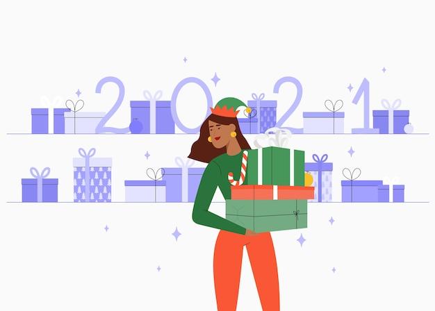 Une jeune fille ou l'aide du père noël tient une montagne de cadeaux. en arrière-plan, une montagne de cadeaux.