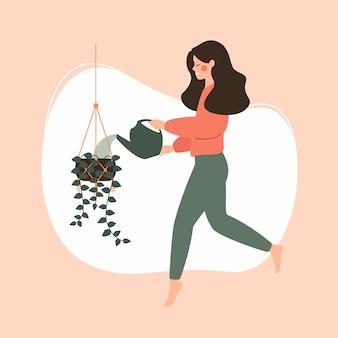 Jeune fille arrosant une plante suspendue en pot.