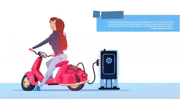 Jeune fille assise de scooter électrique chargeant au transport hybride de moto vintage rouge de station