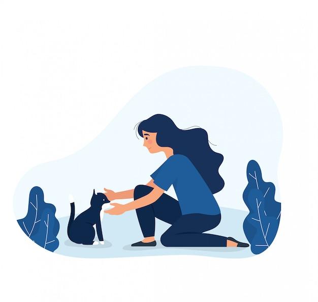 Jeune fille caresser un chat dans le parc