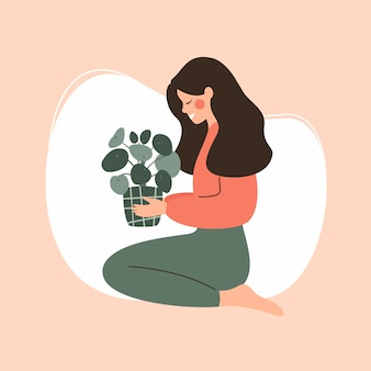 Jeune fille détient une plante verte en pot