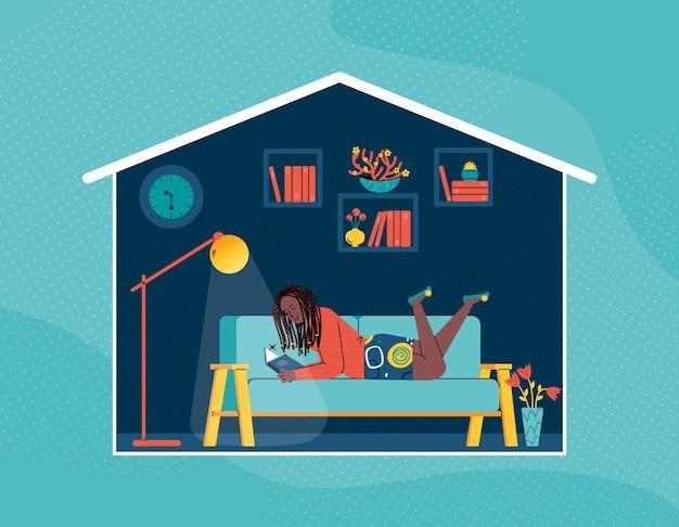 Une jeune fille est allongée sur le canapé et lit un livre près du lampadaire.
