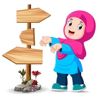 La jeune fille est debout à côté du poteau indicateur et montre le bon chemin