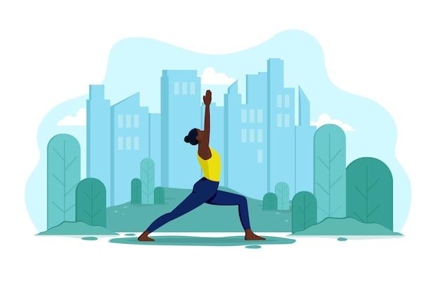 Une jeune fille mince et flexible d'apparence africaine fait du yoga en plein air dans un parc. fille sur le fond de la ville et des arbres fait des exercices