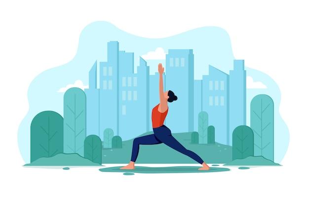 Jeune fille mince flexible fait du yoga en plein air dans le parc. concept de mode de vie sain et de sports de plein air. la fille sur le fond de la ville et des arbres fait des exercices, se détend.