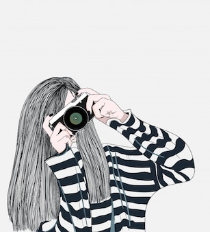 La jeune fille tenant un appareil photo élégant