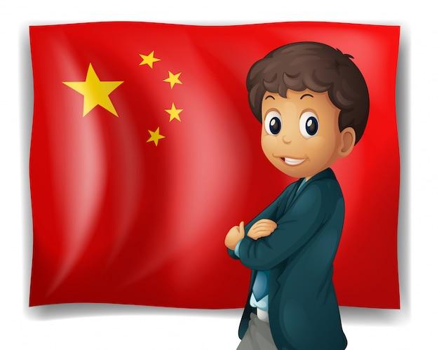 Un jeune garçon devant un drapeau chinois
