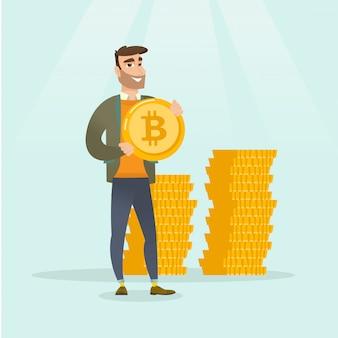 Jeune homme d'affaires prospère avec une pièce de monnaie bitcoin.