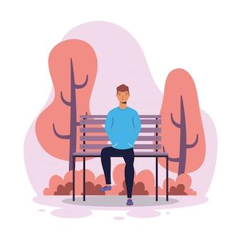 Jeune homme assis dans la chaise de parc