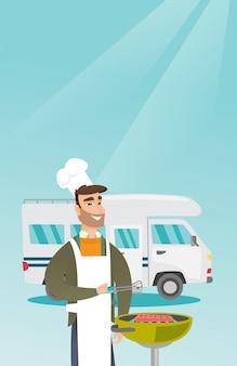 Jeune homme au barbecue de viande devant le camping-car.